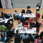 Image shows staff sitting at tables working together at the staff conference, April 2017